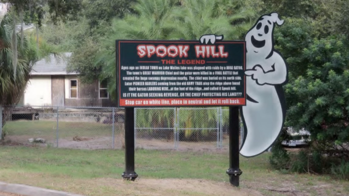 sign detailing the legend of spook hill with cartoon ghost