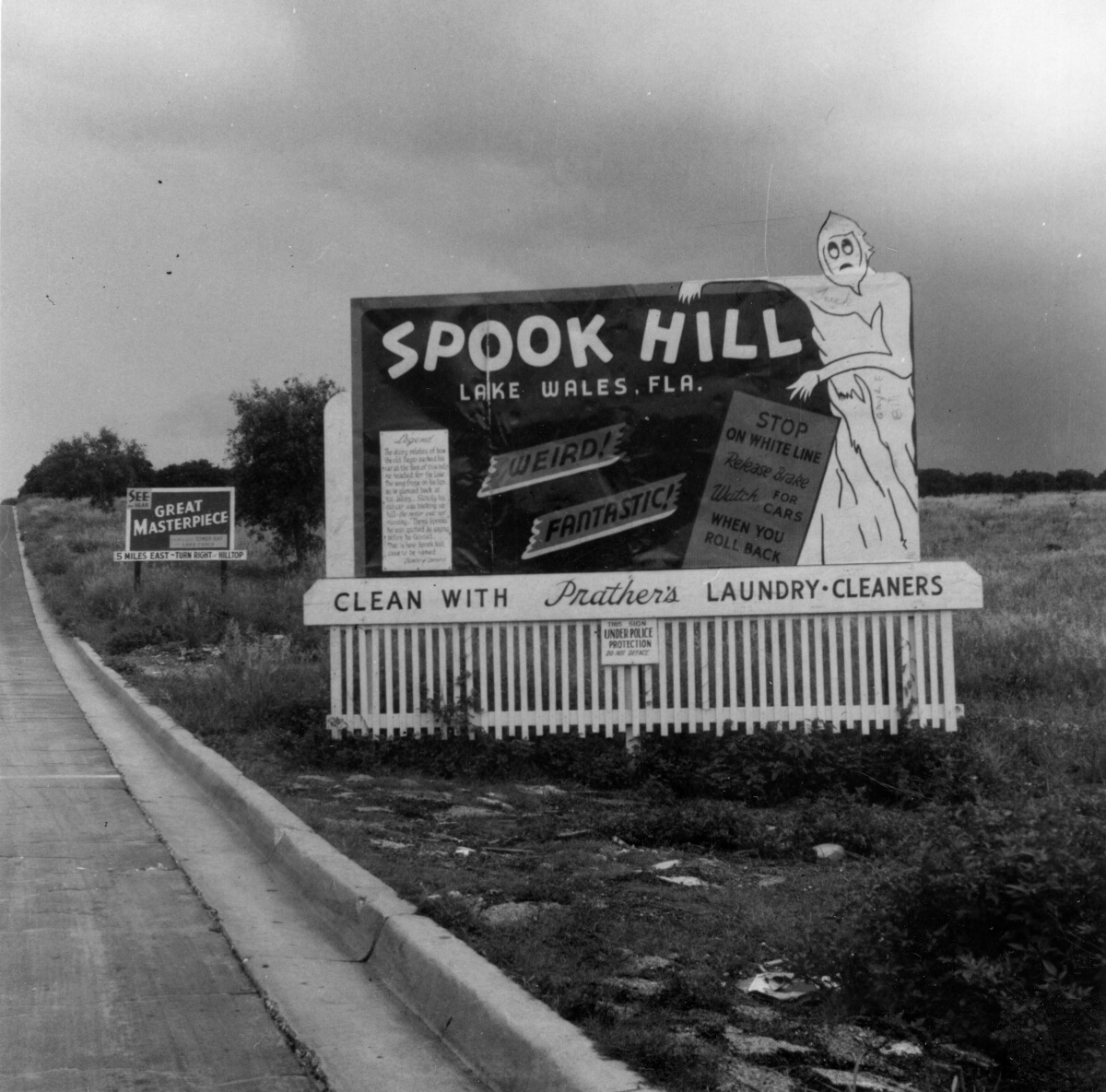 vintage black and white photo of road sign for spook hill