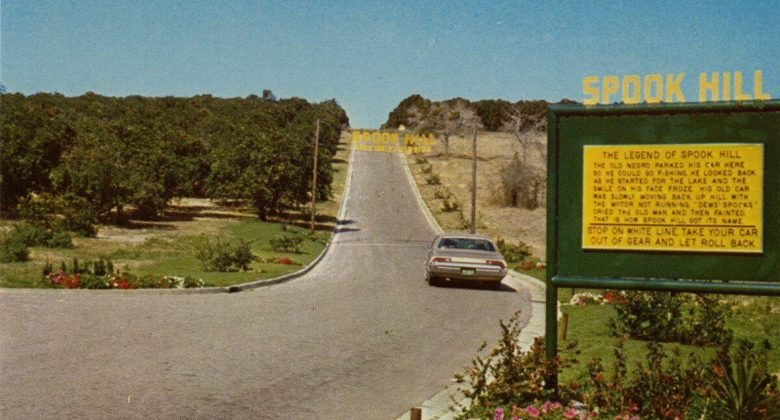 vintage color photo of car with a sign of spook hill